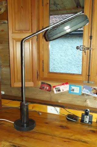 LAMPE DE BUREAU réalisée avec : un engrenage, un axe de moyeu de charrette, un abreuvoir pour les poules et des piquets de tente